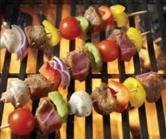 Bison steak and vegetable kabobs on a flaming grill